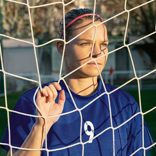 Eugenie Le Sommer holding the net of a football goal and staring into the distance.