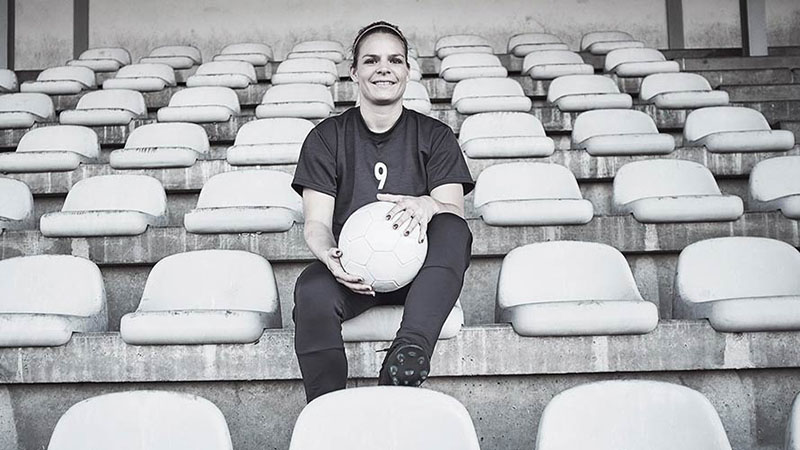 Eugenie Le Sommer sitting in football stadium and holding a football in her lap.