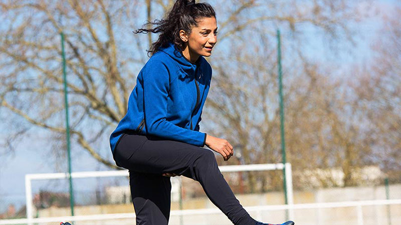 Nadia Nadim doing stretches on the field.
