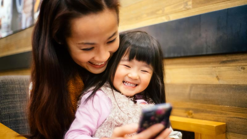 Mom and toddler girl using smartphone joyfully.